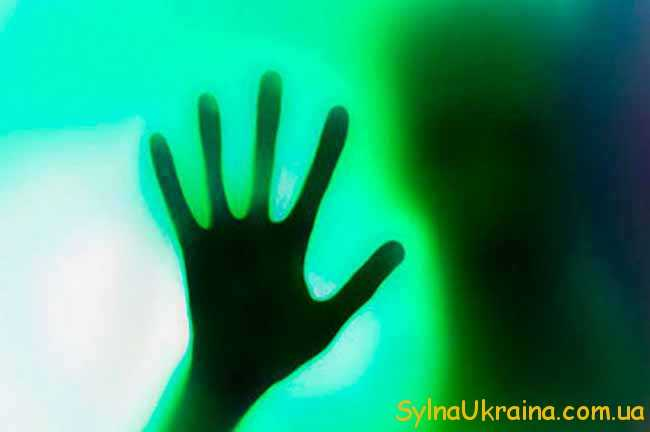рука за зеленим склом